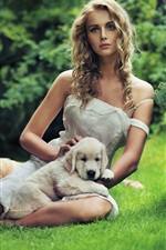 Beautiful girl with a dog in the grass