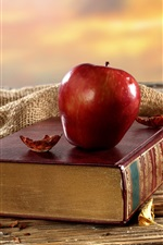 Old book, red apple, desk, window, dry leaves