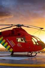 Preview iPhone wallpaper Red helicopter at city sunset