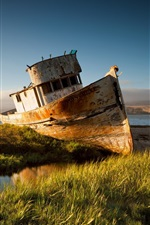 A broken ship, sunset, river, grass