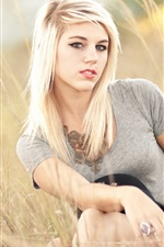 Blonde girl in the summer grass