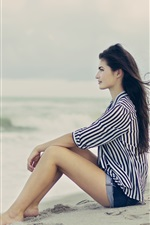 Preview iPhone wallpaper Brunette, girl sitting beach, sand, wind