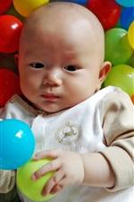 Bebê bonito em bolas de jogo