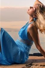 Beautiful blue dress girl, sit at seaside, wind