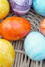 Preview iPhone wallpaper Colorful colored Easter eggs in basket