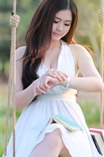 Asian girl sit at swing, white dress, books