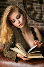 Blonde girl reading book on sofa