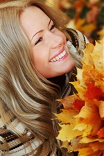 Smile girl in autumn, holding the maple leaves