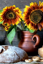 Still life, dry bread, sunflowers, vase, cookies