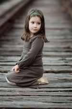 Cute little girl sit at railroad, child, look back