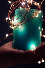 Blue candle, lights, hand