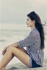 Preview iPhone wallpaper Brunette hair girl sitting at the beach, sea, wind