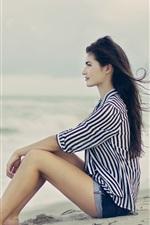 Brunette hair girl sitting at the beach, sea, wind