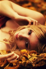 Preview iPhone wallpaper Blonde girl lying on the ground, leaves, autumn