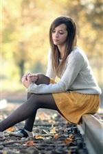 Girl sit on railroad, autumn, bokeh