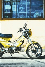 Yellow motorcycle, city street