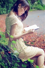 Asian girl reading book, road, leaves