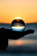 Bola de vidro à mão, por do sol, à noite