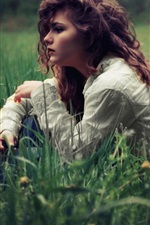 Curly hair girl sit in grass