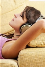 Girl lying on sofa, headphones