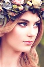 Rapariga loira, coroa de flores, olha para o lado