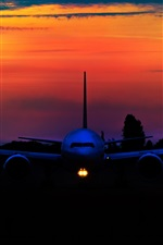 Preview iPhone wallpaper Airplane at sunset, front view, night