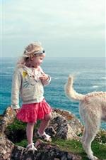 Cute criança garota e cachorro andam à beira-mar