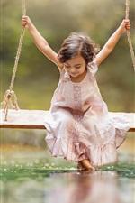 Happy little girl play swing, water