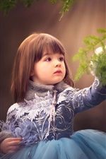 Lovely child girl touch spruce twigs