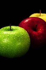 Three apples, green, red, yellow, black background