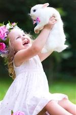 Criança feliz brinca com coelho branco
