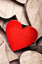 Many wooden love hearts, one red