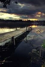 Preview iPhone wallpaper Pier, lake, bridge, grass, black clouds, dusk