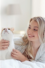 Happy blonde girl and cat in bed