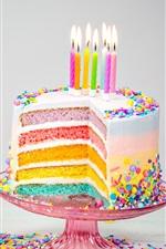 Bolo de aniversário de cores do arco-íris, velas, chama