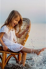 Cute little girl sit on chair to play water