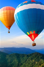 Two hot air balloons, mountains, sky