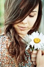 Brunette girl, chamomile in hands