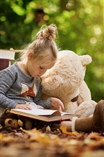 Cute child girl reading book, toy bear
