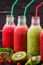 Quatro garrafas de suco de frutas, kiwi, bagas