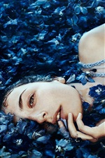 Preview iPhone wallpaper Girl lying on blue flowers sea