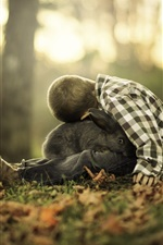 Little boy and black rabbit, forest