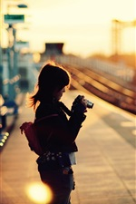 Preview iPhone wallpaper Little girl use camera, rail station, sunset