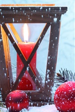 Red Christmas balls, candle, flame, snow, twigs
