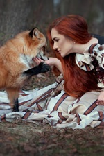 Red hair girl and fox sit on ground