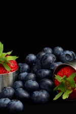 Blueberries and strawberry, black background