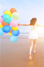 Happy girl, back view, beach, colorful balloons, summer