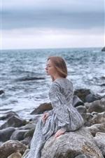 Garota solitária, pedras, mar