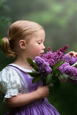 Cute little girl and lilac flowers
