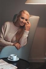 Preview iPhone wallpaper Happy blonde girl, smile, sofa, lamp, book, cup